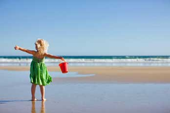 girl standing on beach with a bucket, CA